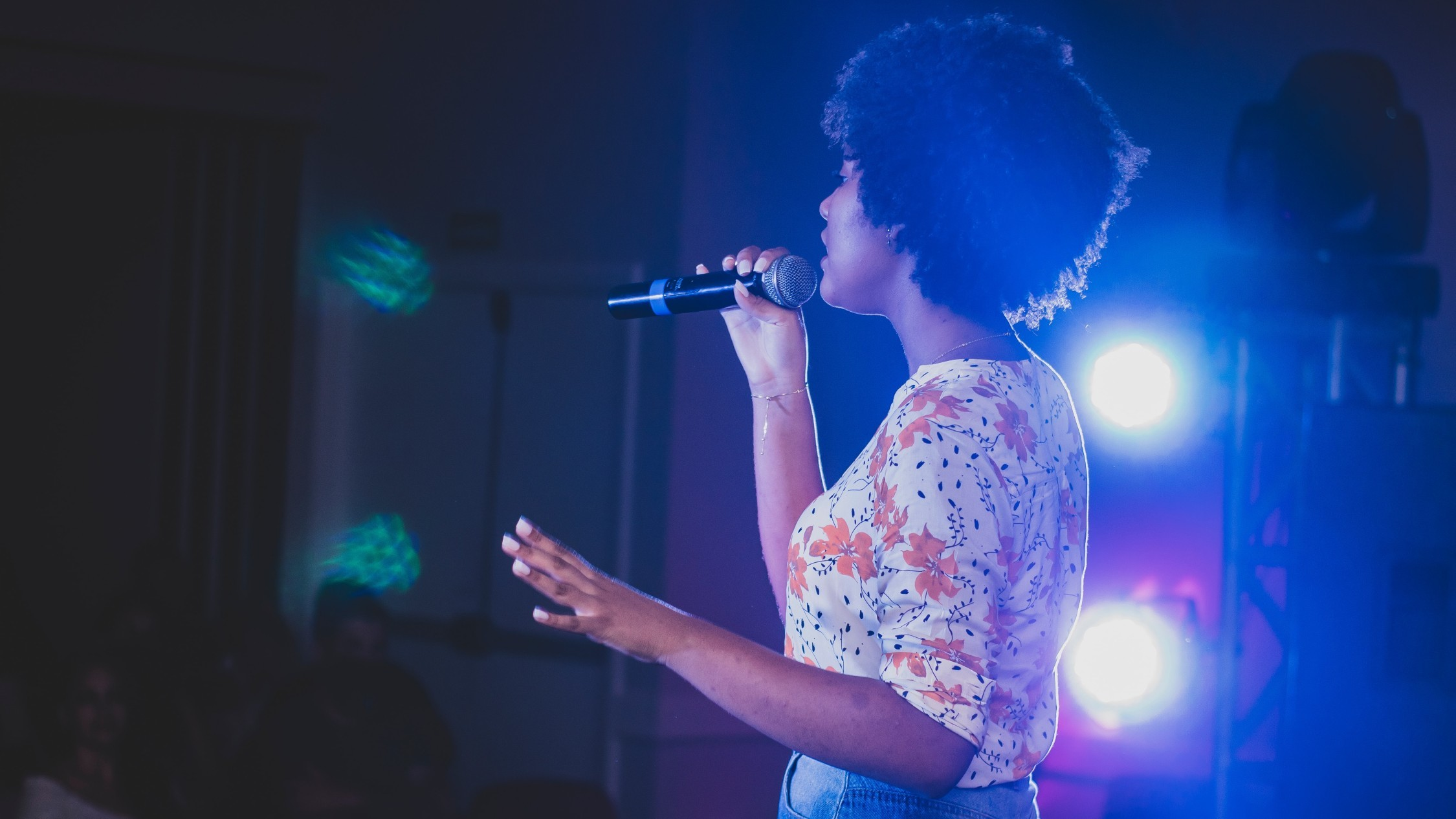 A woman singing karaoke on stage.