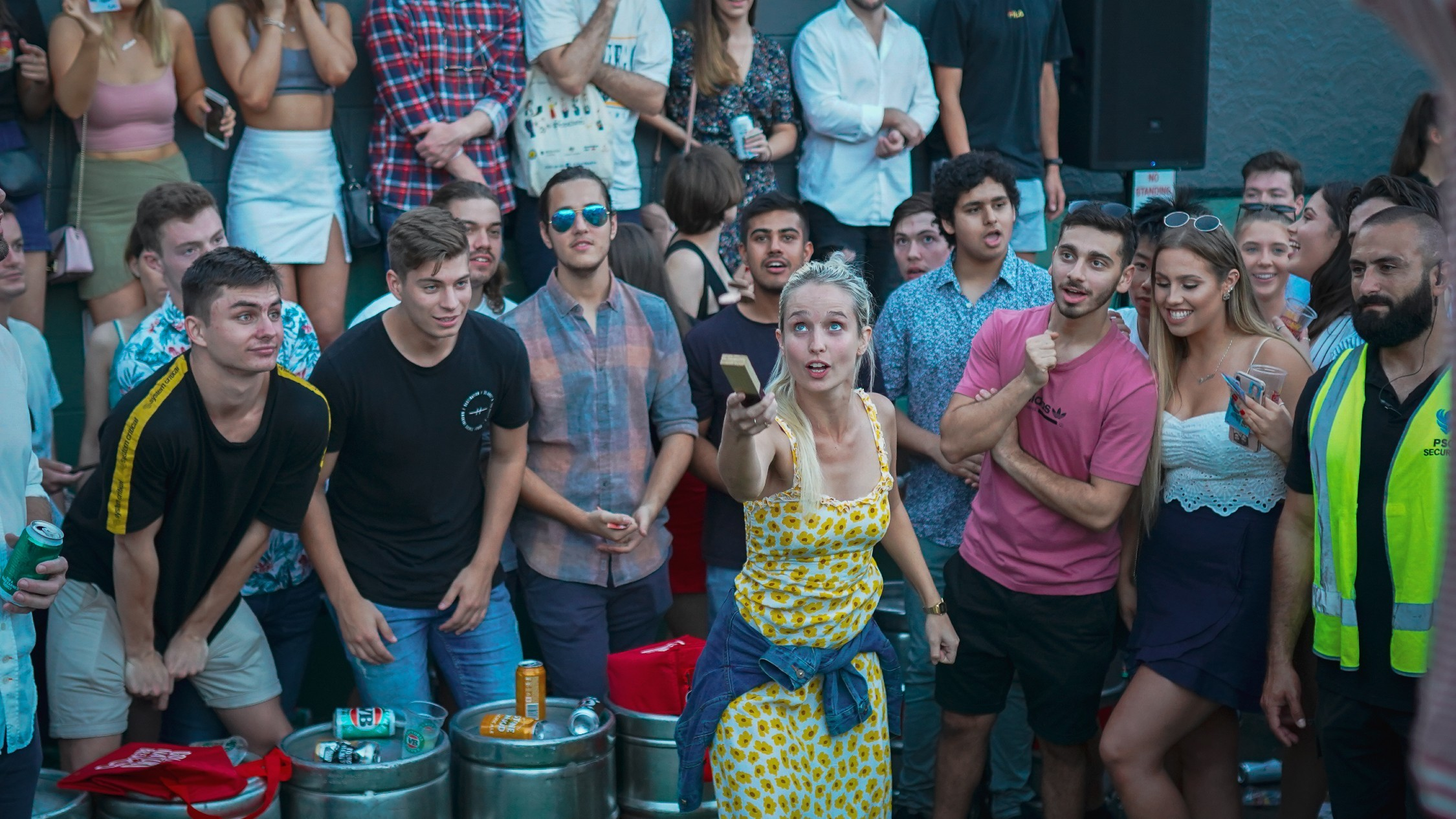 People play two-up, a woman in yellow dress flips coins as the crowd watches on.