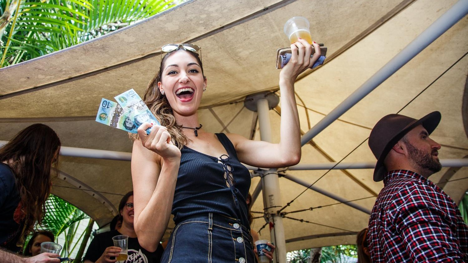 Woman holds up $10 notes and a beer, she is smiling.