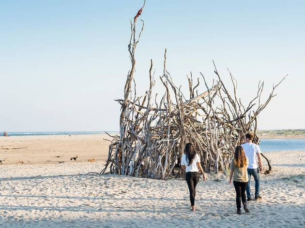People admire a giant pile of driftwood fashioned into a pointed hut or structure on a white sand beach.