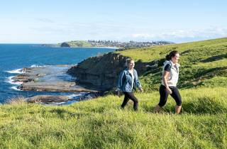Two people walk through long, vibrant green grass on an ocean front headland. The sea and rocks can be seen in the background.