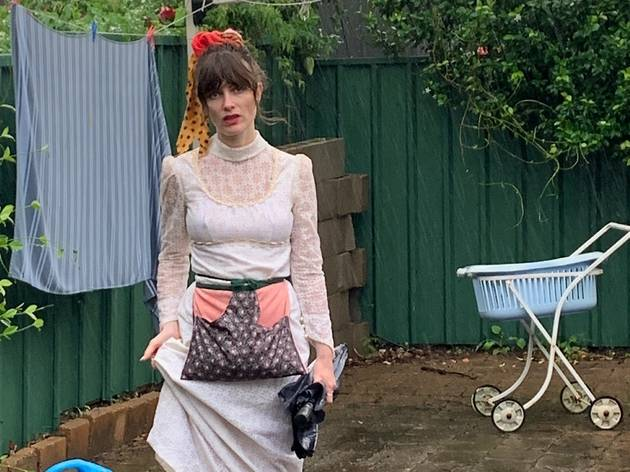 Comedian Beth McMullen poses in front of clothesline in white lace dress, wears pouch around waist.