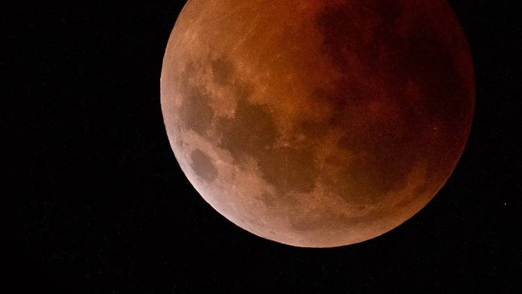 Close up of the Moon during lunar eclipse, the surface glows red and craters are visible.