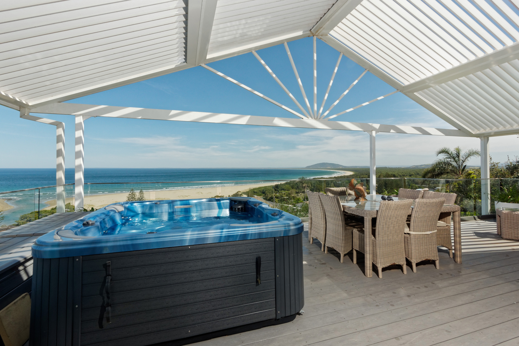 A bright blue hot tub and some table and chairs sit on an expansive balcony overlooking Seven Mile Beach.