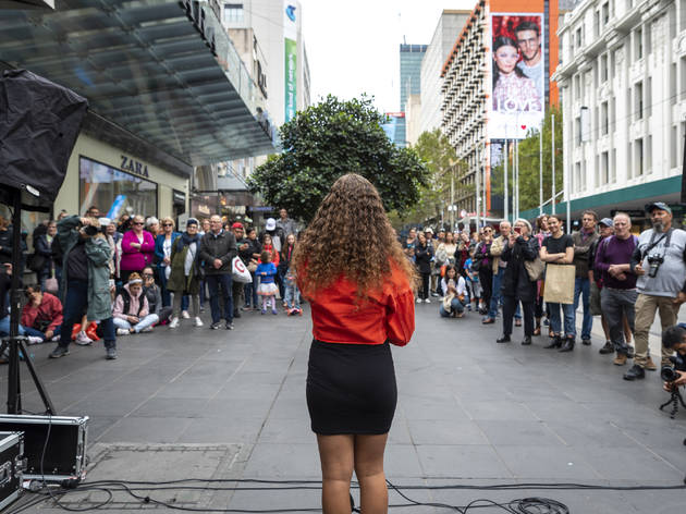 A woman with a red jumper, black skirt and long curly brown hair performs to a crowd in Bourke Street Mall.