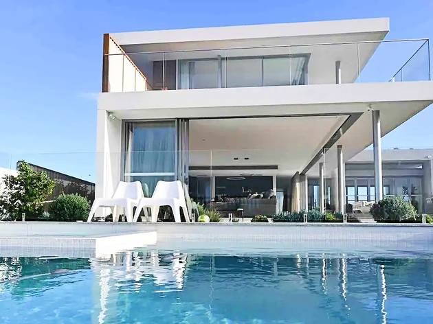 Giant white walled house with pool in front