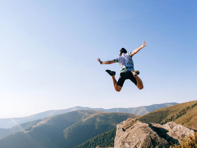 Man jumps from cliff in mountains aka base jumping