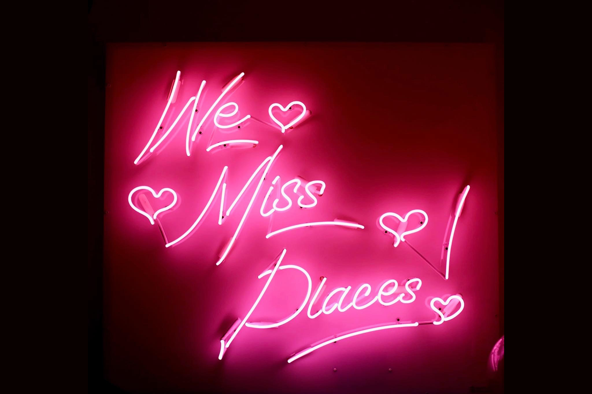 Neon sign that says We Miss Places