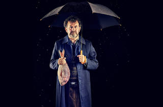 A bearded man stands in front of a dark black background. He is wearing a navy blue raincoat and holding a black umbrella in one hand and a red fish in the other.