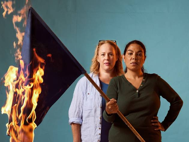 Two women, one holding a burning flag