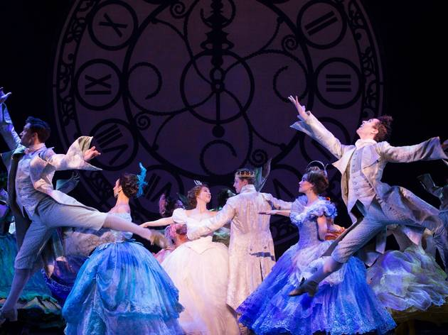 Cinderella dances with the prince in front of a giant clock at the ball