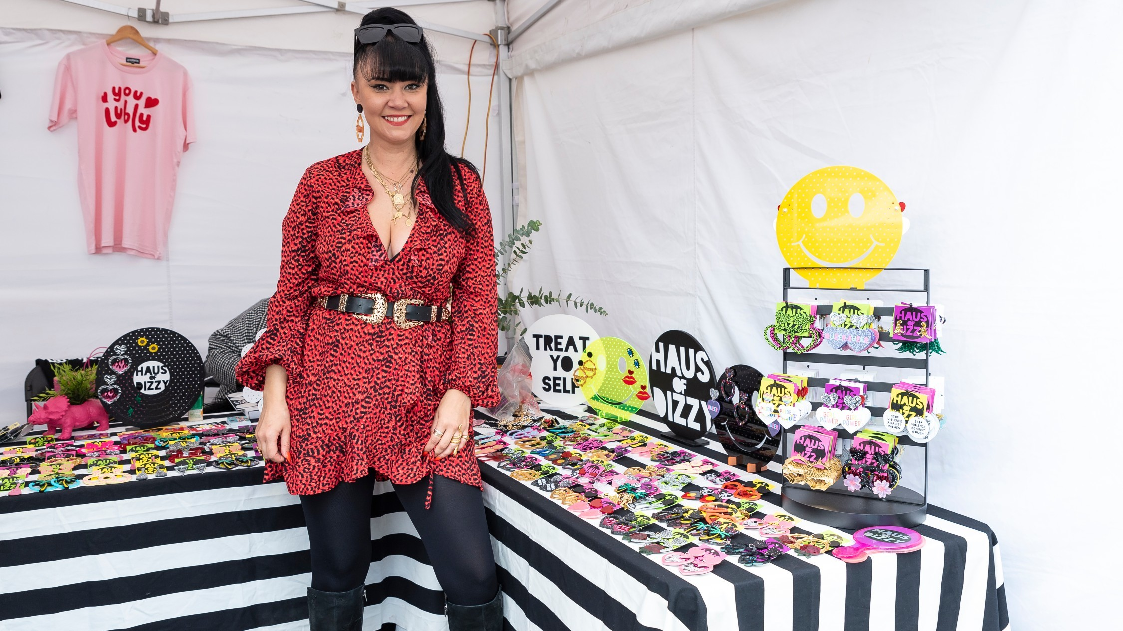 A woman with long dark hair tied in a high ponytail stands in front of colourful jewellery inside a white market tent. She is wearing a red and black ruffled blouse with a chunky belt and smiling.