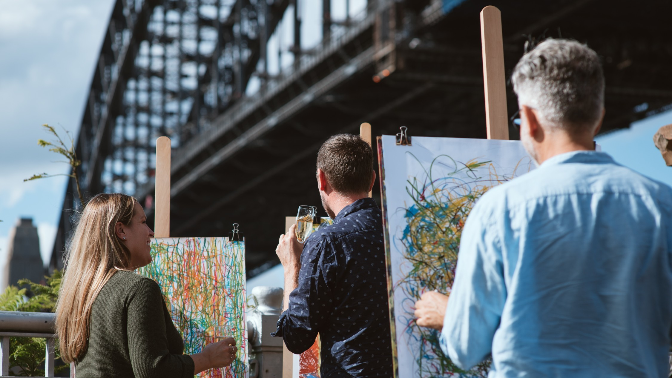 People with easels create scribbly drawings, they hold wine glasses, the Sydney Harbour Bridge is in the background.