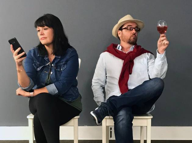 A woman on a phone and a man holding up a glass of red wine