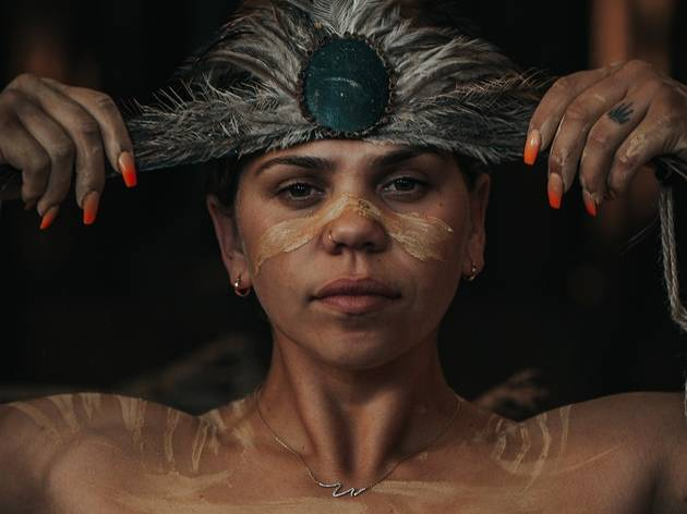 A woman with bright red nails and markings painted on her face and shoulders puts a feathered headband up to her forehead