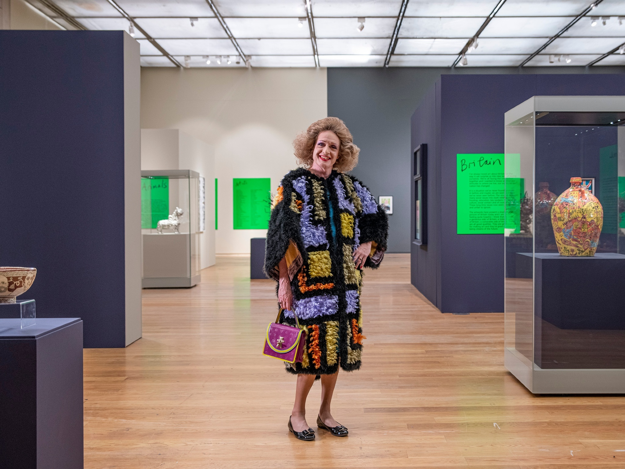 Grayson Perry in crotchet dress with wig and handbag inside gallery space