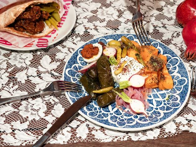 Plate of food with dips and pickles on a white tablecloth