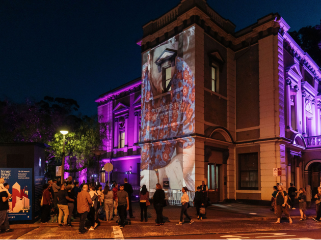 Leichardt Town Hall with purple and video projections on its facade at night.