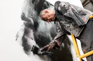 An elderly man with short white hair and only one warm meditatively smears black paint on a white wall. He is covered in black paint too.