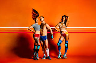 A man and two women strike poses. All three are wearing skimpy activewear; the man is shirtless and the two women have long socks and roller skates on.