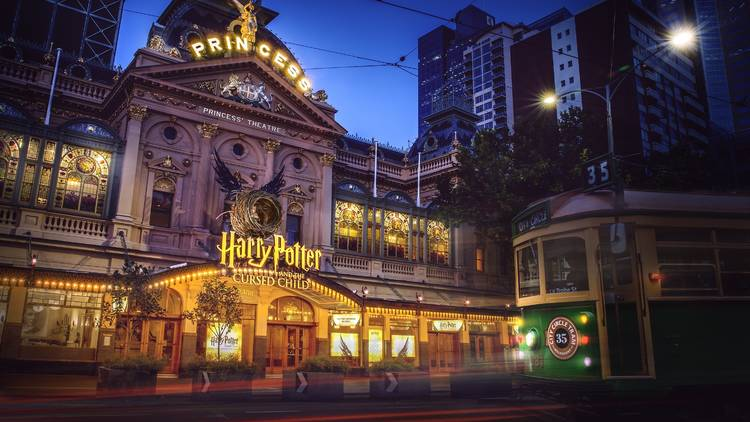 Exterior of the Princess Theatre at dusk. The theatre is lit up by fairy lights and the glowing Harry Potter and the Cursed Child sign. A city circle tram goes by in the foreground