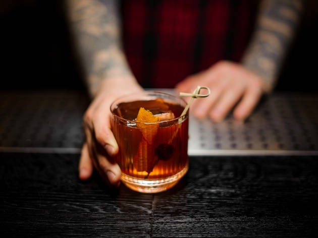 Bartender serving an Old Fashioned
