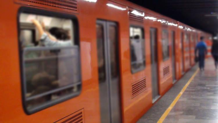 Interior del estación de metro con vagones naranjas