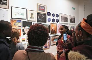A group of people photograph an artist on their phones as she stands in front of a wall of artworks