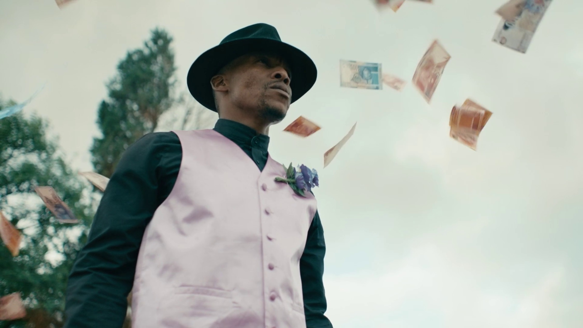 A man in hat and pink waistcoat rained on with with bank notes
