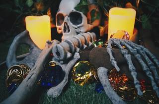 A skeleton lies between two large candles. Beneath it are jewels and coins.