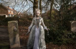 A ghostly figure in pale make up and gown stands in a wood next to a large stone gatepost