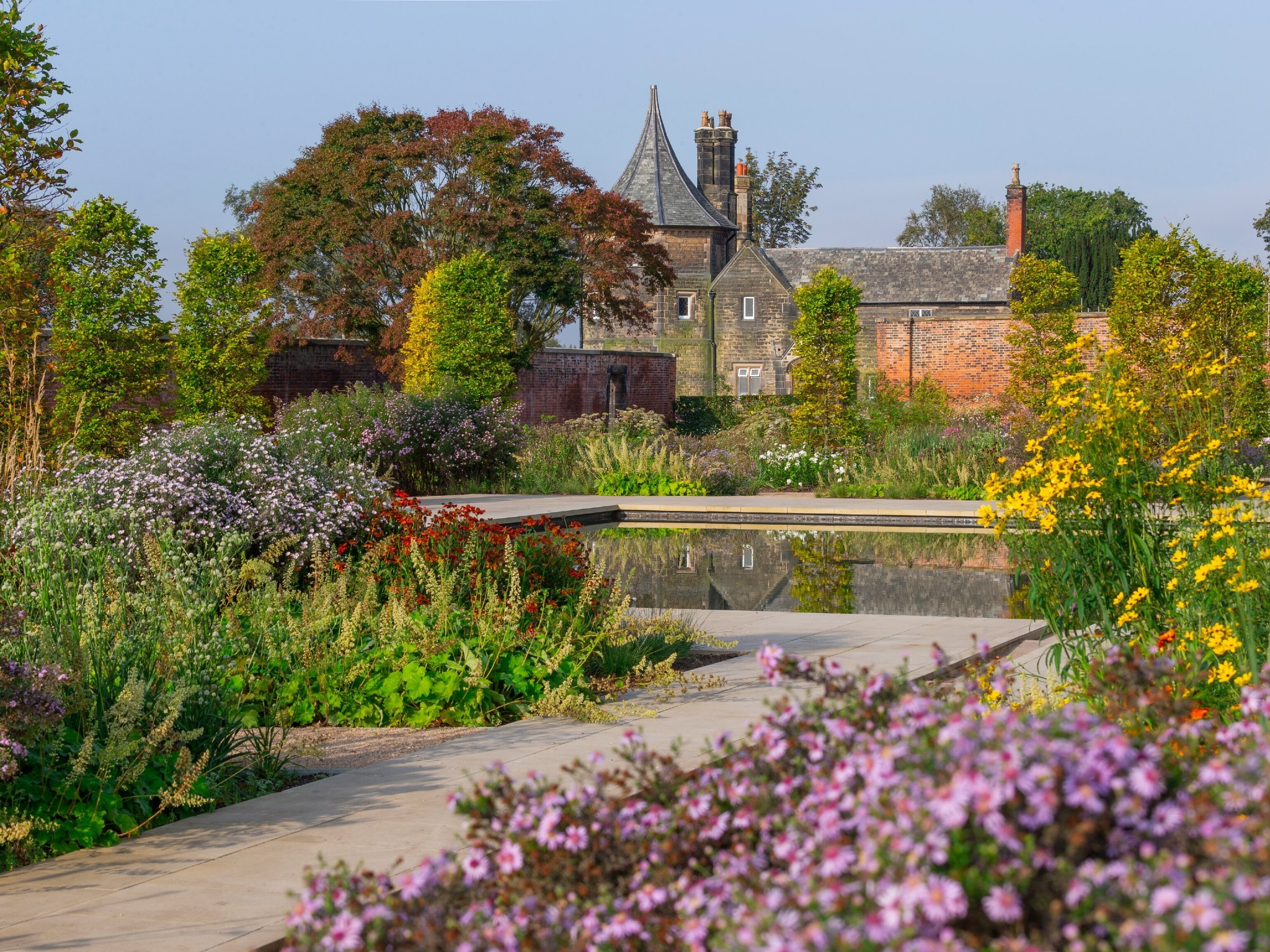 A pathway surrounded by flowers leads to a formal pond which is all overlooked by an old red-brick house