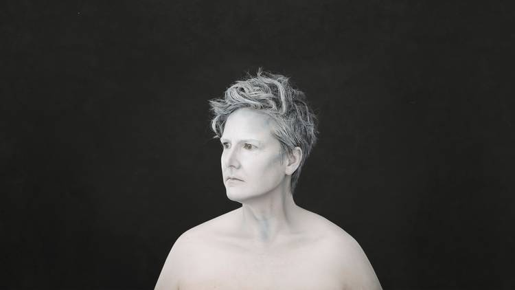 A black and white portrait photograph of Hannah Gadsby taken from the shoulders up.. She is stoically turning her face to the side and is wearing wearing no shirt. She appears like a marble statue.