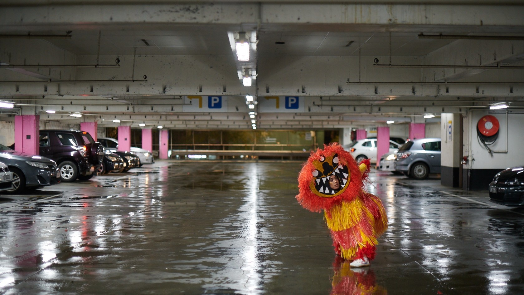 Someone dressed as a lion in a carpark
