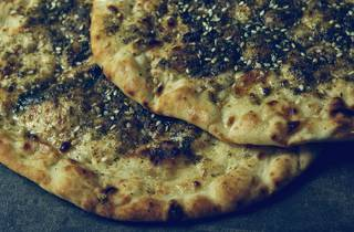 Two pieces of Zaatar, a Middle Eastern flatbread topped with oregano and seasame seeds.
