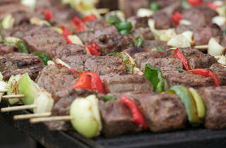 Row of meat and vegetable skewers are lined up on a grill.