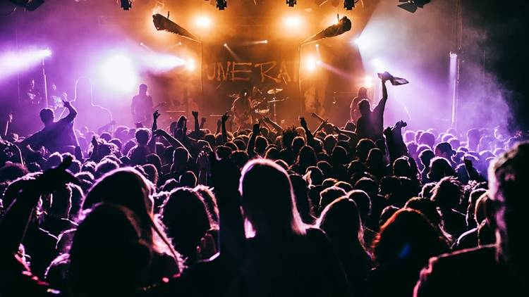 A view through a packed crowd with their hands in the air watching a band perform on the stage at the Metro.