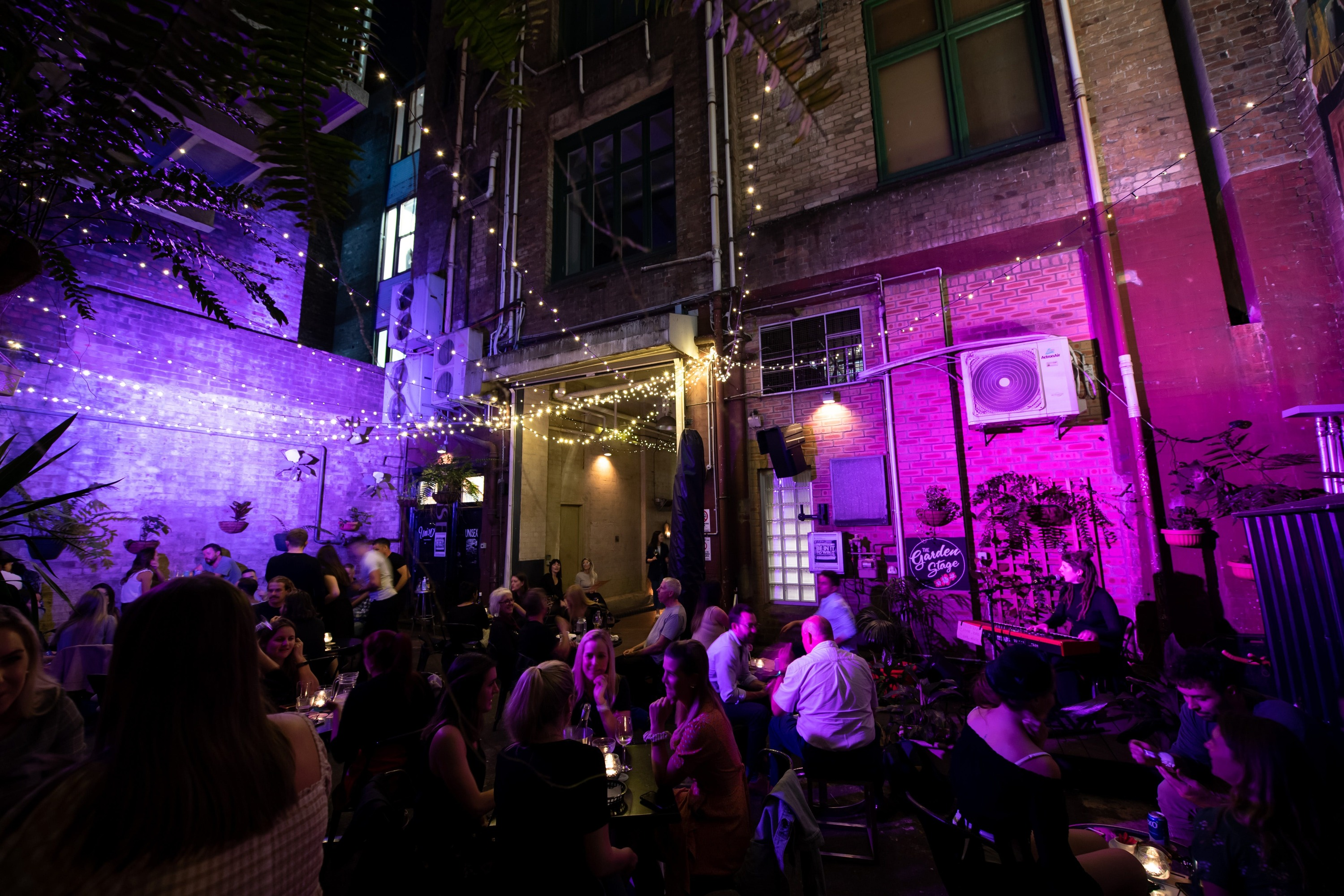 A purple-lit laneway scene with people sitting down eating and drinking