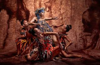 A group of people in earthen colours create a pyramid of bodies against a red rocky backdrop