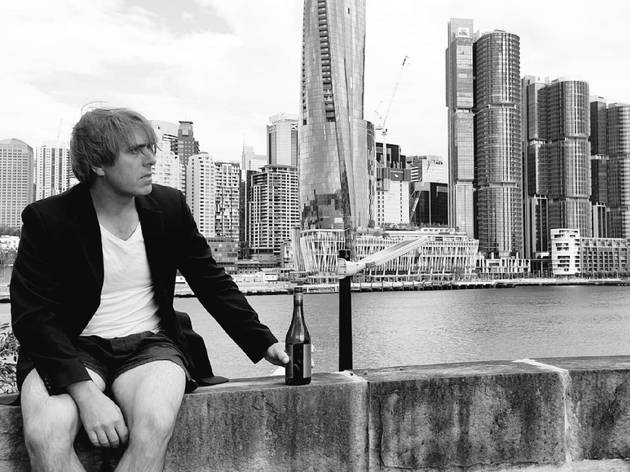 A man with no pants cradles a beer in front of Sydney city skyline