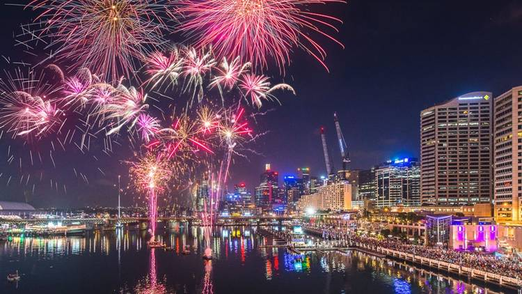Hot pink and gold fireworks going off over Darling Harbour.