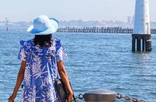 A woman faces the ocea while wearing a sun hat and blue dress. She is carrying a lot of luggage