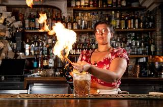A person holds a large flame over a cocktail at a bar.