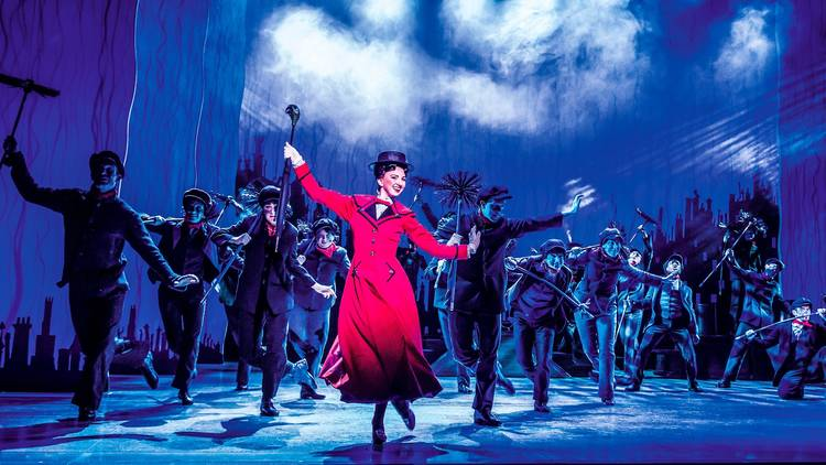 Production shot form Mary Poppins shows Mary in red costume dancing with chimney sweeps