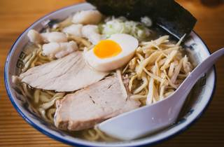 A bowl of ramen in a blue and white china bowl. There is a white spoon in the bowl and the ramen is topped with two thick slices of pork, half a soft boiled egg and a slice of dried seaweed