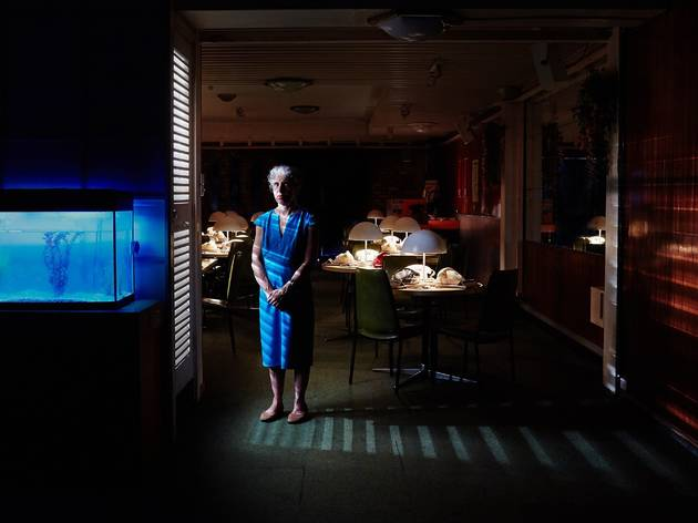 A woman in a blue dress stands half lit in a dark room. The room is filled with tables that have lamps on them