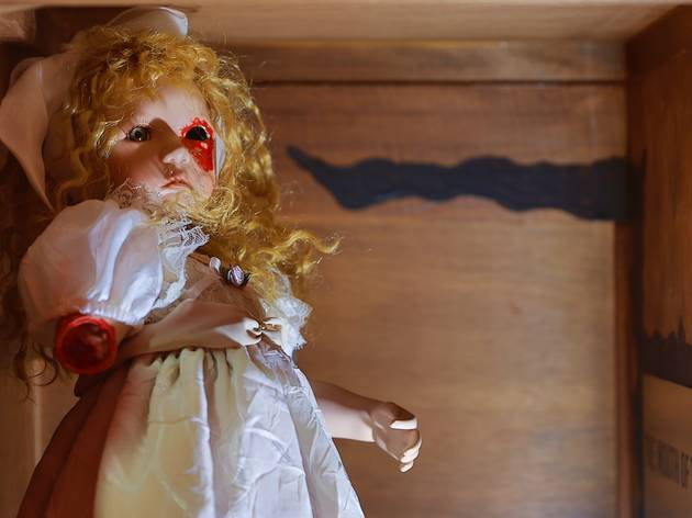 A porcelain doll wearing a white dress and with long curly blonde hair in a wooden box. The doll is missing an arm and an eye and red paint has been used to look like blood on the missing body parts