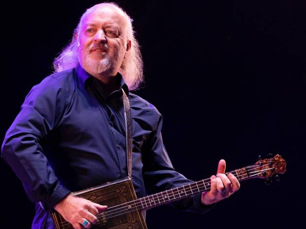 Comedian Bill Bailey on stage playing a guitar made out of a book