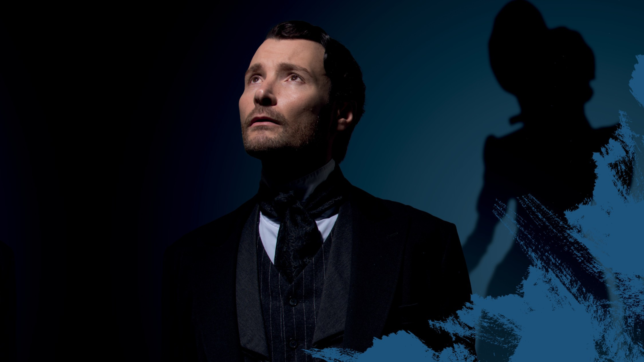 A man in a black suit and tie, with the ghostly figure of a woman behind him