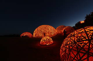 Glowing orange mesh baubles large enough for a person to stand in in a dark field